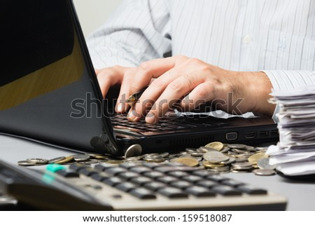 Businessman typing on laptop keypad with coins, bills and calculator - stock photo