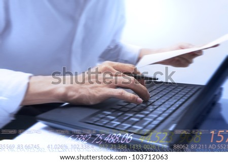 businessman typing on notebook and running numbers - stock photo