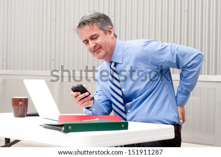 Businessman under stress, fatigue and pain at the office - stock photo