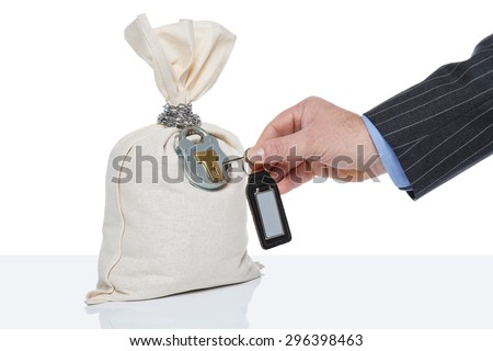 Businessman unlocking a money sack, white background, blank tag on key fob. - stock photo