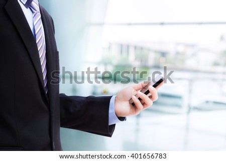 Businessman use smartphone on blur of office background - stock photo