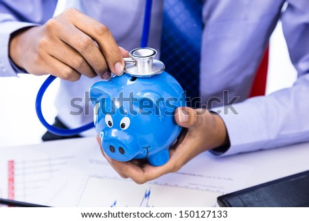 Businessman use stethoscope with piggy bank for financial health check concept - stock photo
