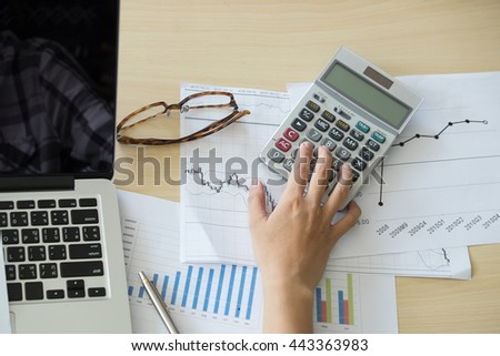 Businessman using a calculator to calculate the numbers top view,vintage effect. - stock photo