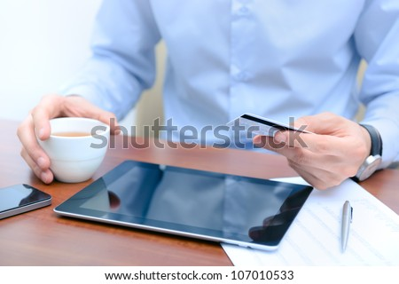 Businessman using a credit card and digital tablet for buying on-line. - stock photo