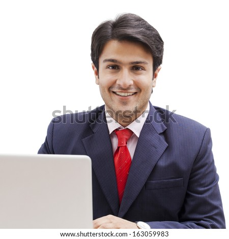 Businessman using a laptop and smiling - stock photo
