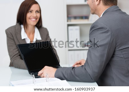 Businessman using a laptop computer in a meeting with a female colleague with focus to the blank screen of the computer - stock photo