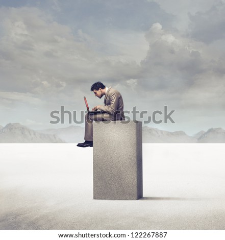 Businessman using a laptop computer sitting on a concrete block in a desert - stock photo