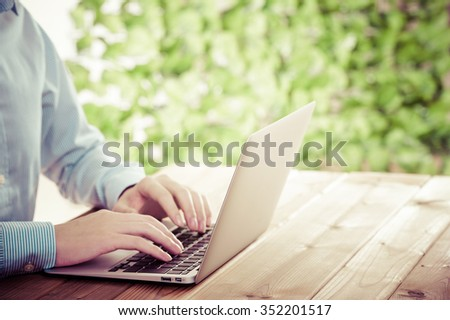 Businessman using a laptop, green background - stock photo