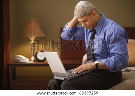 Businessman using a laptop in his hotel room - stock photo