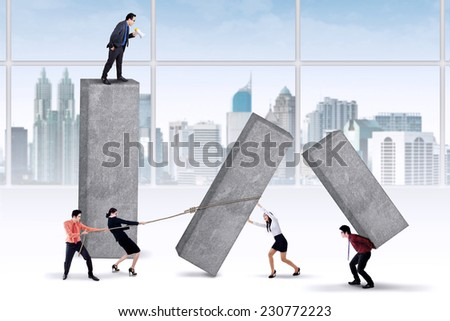 Businessman using a megaphone for commanding his employees to work harder - stock photo