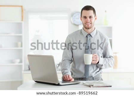 Businessman using a notebook while drinking coffee in his kitchen - stock photo