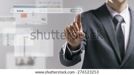 Businessman using a search engine and pressing a search button with web pages on background - stock photo