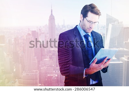 Businessman using a tablet computer against low angle view of skyscrapers at sunset - stock photo