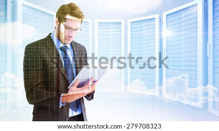 Businessman using a tablet computer against server room - stock photo