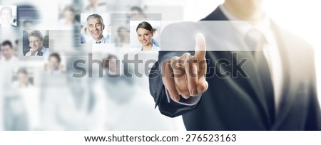 Businessman using a touch screen interface and pushing a button, people avatars and business team on background - stock photo