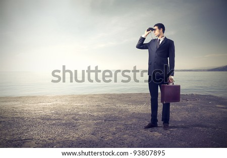 Businessman using binoculars with seascape in the background - stock photo