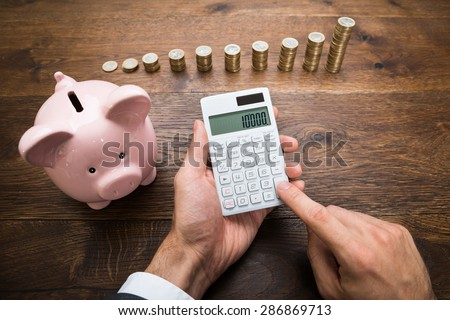 Businessman Using Calculator With Piggybank And Stack Of Coins On Desk - stock photo
