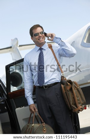Businessman using cell phone with airplane in the background - stock photo