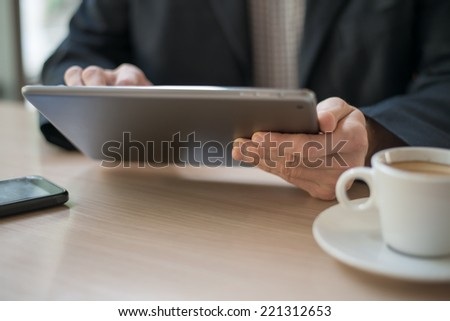 Businessman using digital tablet in cafe - stock photo