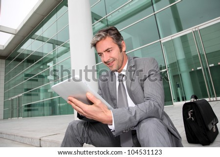 Businessman using electronic tablet in front of offices building - stock photo
