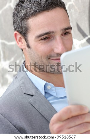 Businessman using electronic tablet outside the office - stock photo