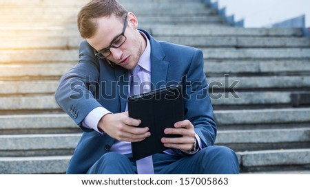 Businessman using electronic tablet pc and mobile phone. He is sitting on a stairs. - stock photo