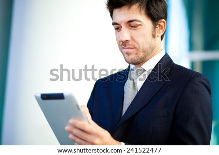 Businessman using his digital tablet - stock photo
