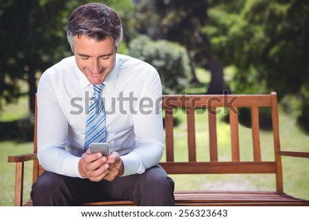 Businessman using his phone in the park on a sunny day - stock photo