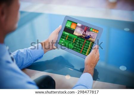 Businessman using his tablet against gambling app screen - stock photo