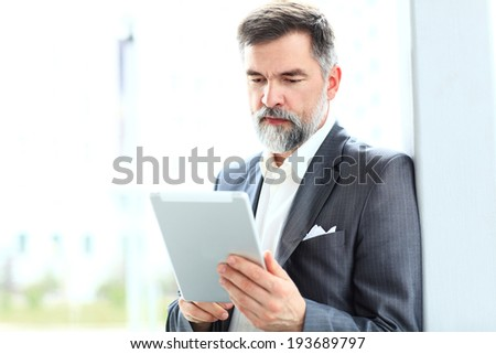 Businessman using his tablet in the office. Business man working with a digital tablet   - stock photo