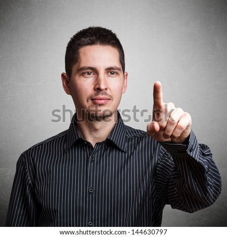 Businessman using invisible touchscreen on grey background - stock photo