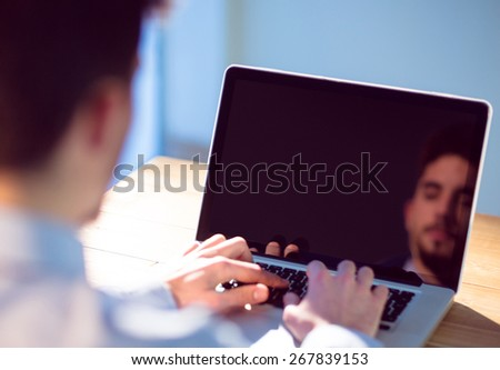 Businessman using laptop at desk shot in studio - stock photo