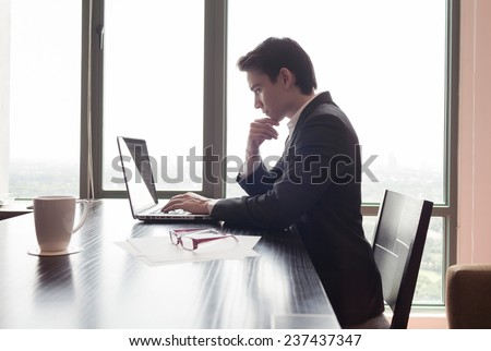 Businessman using laptop computer at the office - stock photo