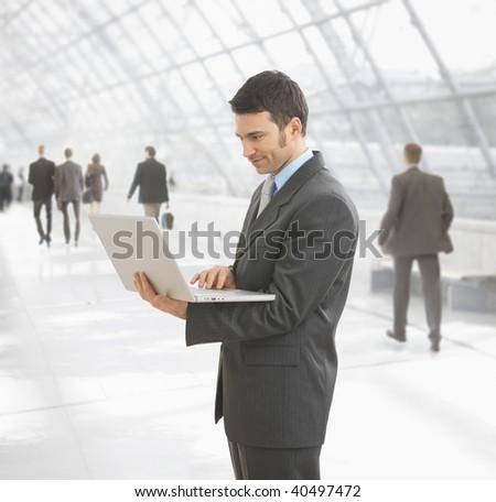 Businessman using laptop computer standing on office hallway. - stock photo