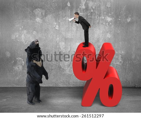 Businessman using megaphone yelling at black bear on red percentage sign with concrete wall and floor background - stock photo