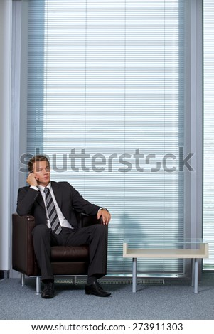 Businessman using mobile phone in office - stock photo