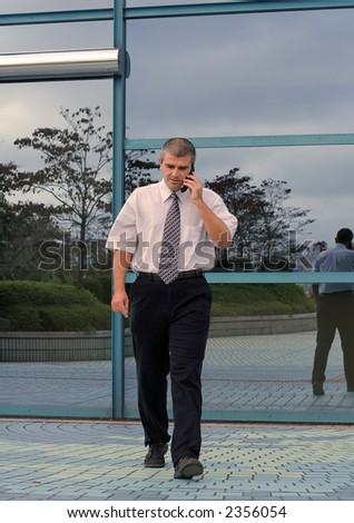 Businessman using mobile phone while is walking in hurry in front of a blue corporate building. - stock photo