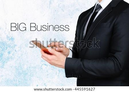 businessman using mobile smart phone near text - BIG Business - stock photo
