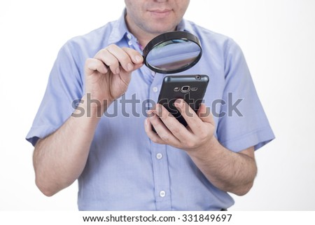 Businessman using mobile smart phone with magnifying glass . Phone fraud concept - stock photo