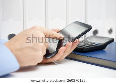 Businessman using modern mobile phone application for accounting in office with documents in background - stock photo