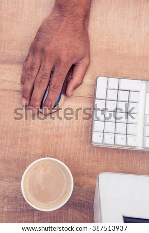 Businessman using mouse by coffee cup while working at wooden desk in office - stock photo