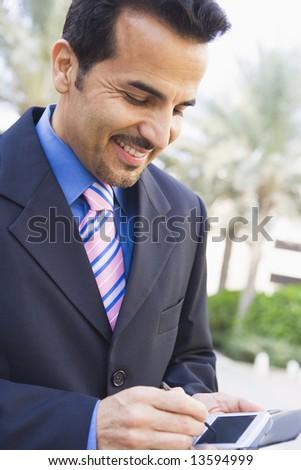 Businessman using PDA outside - stock photo