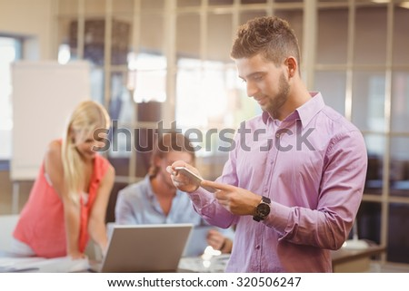Businessman using phone in office with colleagues working in background - stock photo