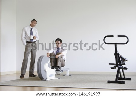 Businessman using rowing machine with colleague standing by - stock photo