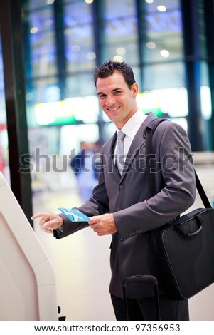 businessman using self help check in machine at airport - stock photo