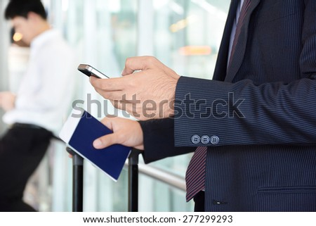 Businessman using smart phone while holding passport in another hand - business travel concept - stock photo