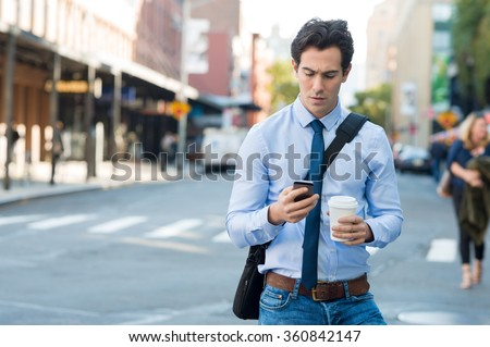 Businessman using smartphone and holding paper cup ina urban scene. Worried businessman walking on the road and messaging with phone.  - stock photo