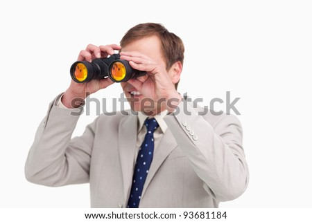 Businessman using spy glasses against a white background - stock photo