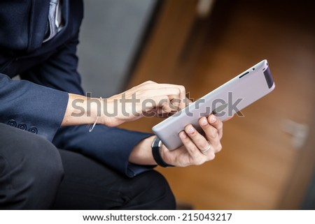 Businessman using tablet at the hotel lobby.  - stock photo