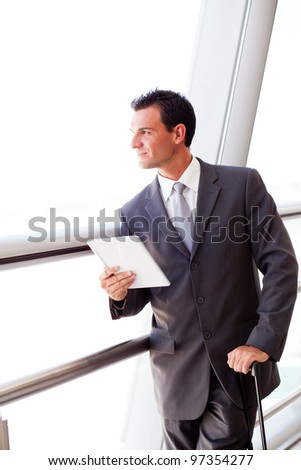 businessman using tablet computer at airport - stock photo
